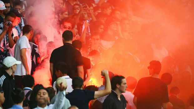 A flare is ignited in the Melbourne Victory supporters area of the crowd.