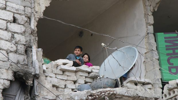 Children peer out from their destroyed home in Aleppo, Syria's largest city.