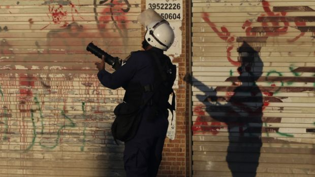 A riot policeman fires tear-gas towards anti-government protesters in Daih, Bahrain.