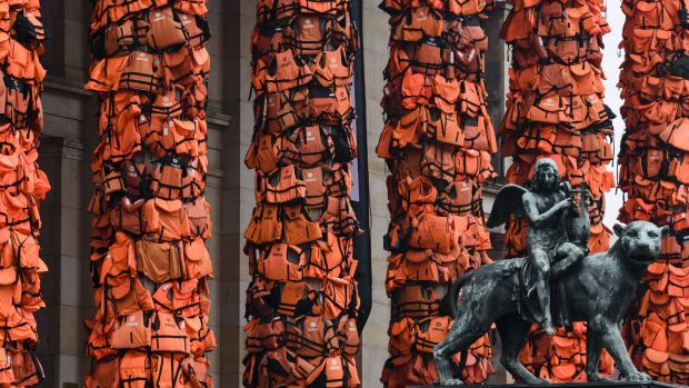 An art installation by Chinese artist Ai Weiwei features refugees' life vests wrapped around the pillars of Berlin's ...