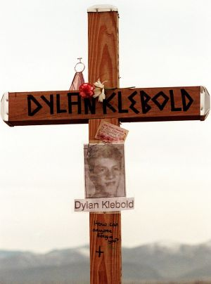 "A cross bearing the name and likeness of Dylan Klebold and a message ""How can anyone forgive you?"" on a hill in ..."