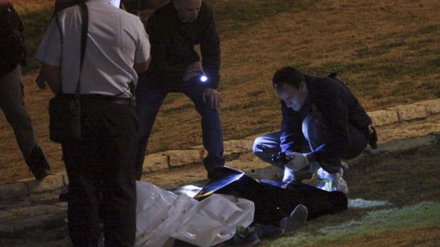 Israeli police examine the body of a Palestinian in Jerusalem on Sunday.