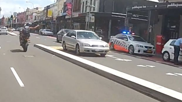 The passenger gestures to police.