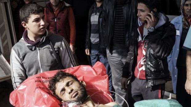 A wounded Syrian man is carried to a hospital in Kilis, Turkey. An air strike in the northern Syrian province of Idlib ...