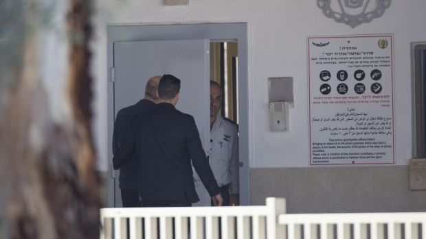 Ehud Olmert, left, enters prison to begin his sentence in the central Israeli town of Ramle.