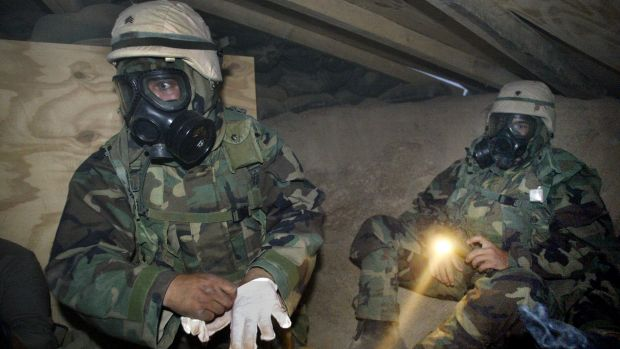 US soldiers in NBC (nuclear, biological, chemical) gear under torchlight in a bunker near camp Doha after a siren ...