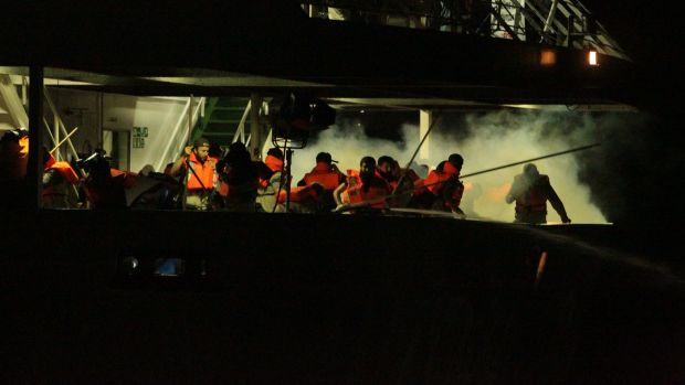 Passengers on the Mavi Marmara run as tear gas is fired by Israeli commandos.