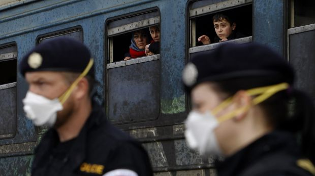 Refugees aboard a train bound for Serbia watch Czech Republic police officers maintaining order at the transit centre ...