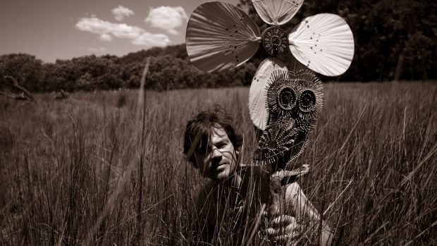 Joshua Yeldham near Sydney's Hawkesbury River with a wooden owl that he carved in 2008.
