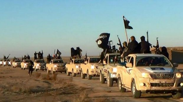 Islamic State militants hold up their weapons and wave the group's flags on their vehicles in a convoy in Raqqa, Syria.
