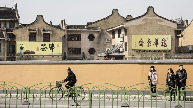 Riding a bicycle past a row of traditional style Chinese buildings near Longhua Temple in Shanghai earlier this month.