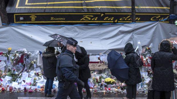 A policeman walks as people pay respects to victims in front of the Bataclan concert hall in Paris after the November 13 ...