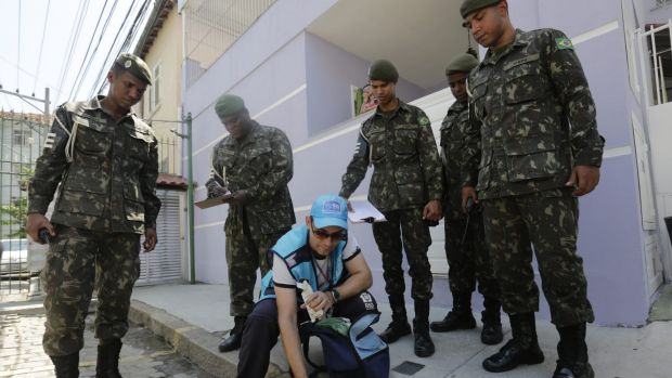 Surrounded by soldiers, a government health agent uses larvicide to kill mosquitos that spread the Zika virus, in the ...