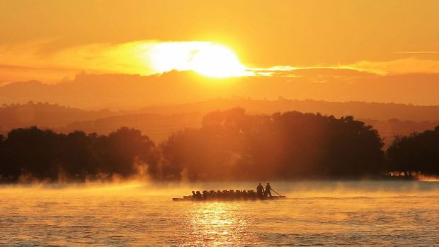 A pair of dragon boats race neck and neck across Lake Burley Griffin, under a scorching summer sunrise.
