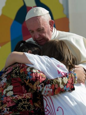 Pope Francis hugs two girls he invited on stage during a meeting with Mexican youth at the Jose Maria Morelos y Pavon ...