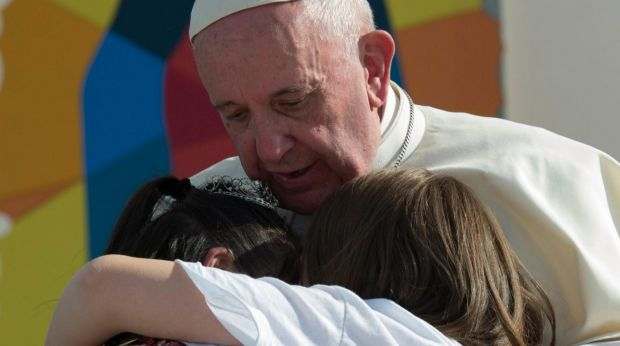 Pope Francis hugs two girls he invited on stage in Morelia on Tuesday.
