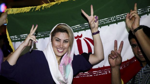 An Iranian woman shows the victory sign as people celebrate on the streets of Tehran following the landmark nuclear deal.