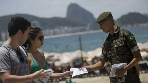 A soldier distributes a pamphlet about the mosquito that spreads the Zika virus on the edge of the Copacabana beach in ...