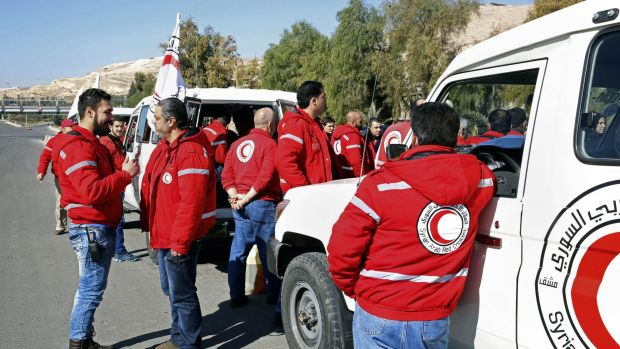 Staff from the Syrian Arab Red Crescent get ready to accompany a convoy of humanitarian aid into the government besieged ...