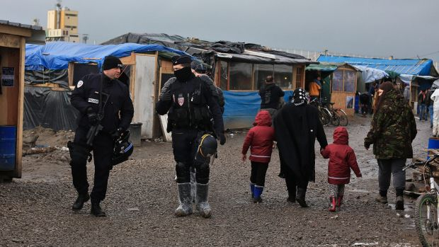 French riot police officers patrol in the migrant camp in Calais, north of France, earlier this month.