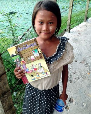 """A girl from the island of Seikkyi, one of Myanmar's poorest neighbourhoods holds the book """"Where women have no doctor"""". ..."""