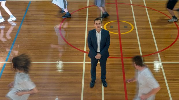 Mr Ferra with students on the basketball court.