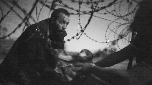 'Hope for a new Life' shows a man passing a baby through a fence at the Serbia-Hungary border in Roszke, Hungary, on ...