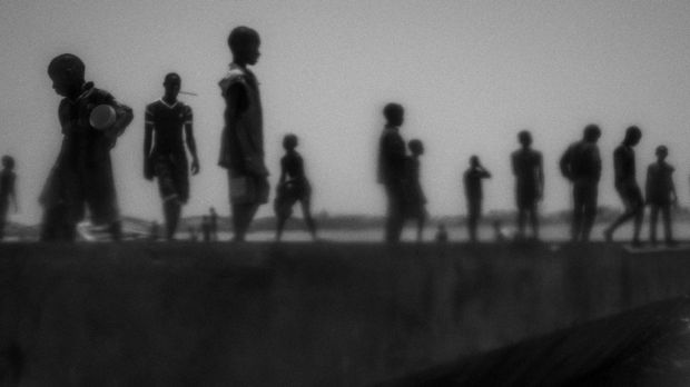 """""""Talibes, Modern Day Slaves"""" by Mario Cruz shows runaway talibes standing on the bank of Senegal river."""