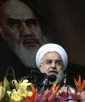 Iranian President Hassan Rouhani delivers a speech under a portrait of the late revolutionary founder Ayatollah Ruhollah ...