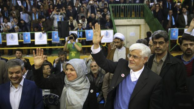 The head of the reformists' coalition list in Tehran, Mohammad Reza Aref, waves to the crowd next to his wife Hamideh at ...