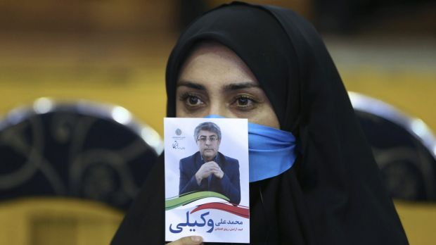 An Iranian woman holds a leaflet showing Mohammad Ali Vakili, a candidate in February 26 parliamentary elections, during ...