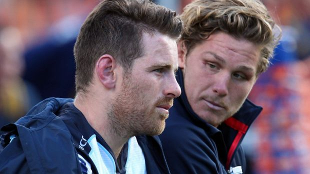 Bernard Foley of the Waratahs sits forlornly on the bench with Michael Hooper after injuring his shoulder.