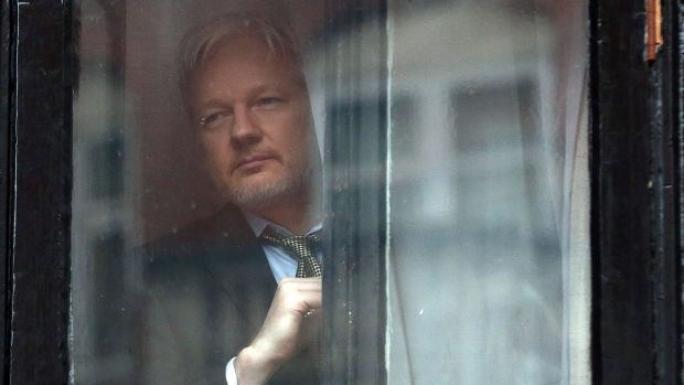 Julian Assange looks out from the Ecuadorian embassy in London,  where he took refuge in June 2012 to avoid extradition ...