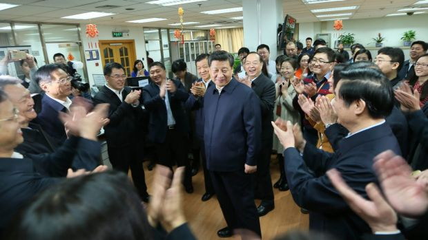 Workers applaud as Chinese President Xi Jinping talks with staff at the <i>People's Daily</i> in February.
