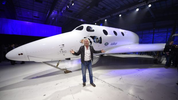 Sir Richard Branson poses in front of Virgin Galactic's SpaceShipTwo space tourism rocket after it was unveiled.