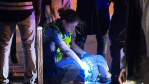 Police mind the injured teenager after the Girrawheen incident.
