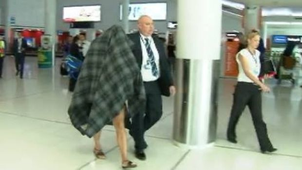 Police escort the accused transgender prostitute from Perth Airport.