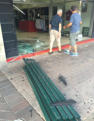 A park bench was knocked down and dragged sideways by the car.