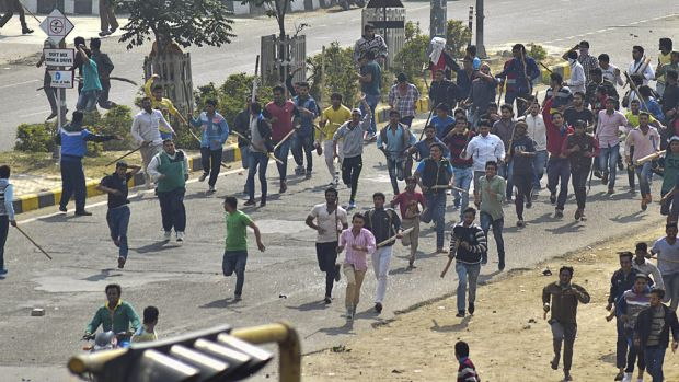 Protesters run during a pro caste quota protest in Rohtak, 70 kilometers (45 miles) west of New Delhi, India on Friday, ...