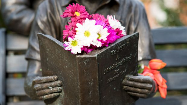 Flowers left on a sculpture in tribute to Harper Lee and her famous novel.