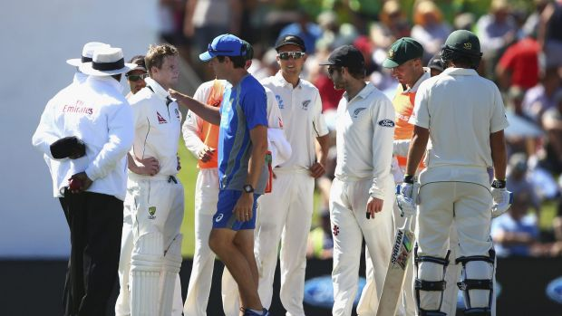 Steve Smith is assessed after being hit by a bouncer.