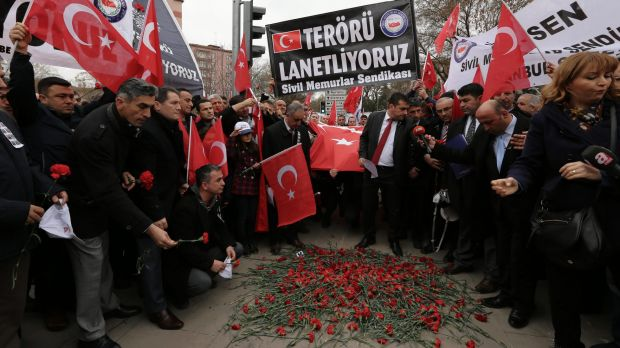 "Turkish civil servants hold a banner that reads "" we condemn terrorism "" as they lay carnations at the site of ..."