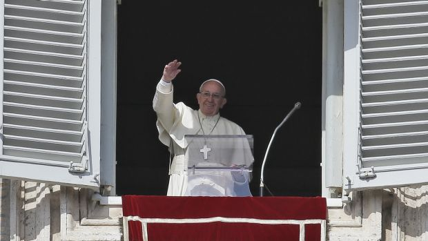 Pope Francis waves to crowds in St Peter's Square. Cardinal Pell says he has the pontiff's backing.