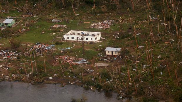 Debris is scattered around damaged buildings at Muamua on Vanua Blava Island in Fiji, after Cyclone Winston tore through ...