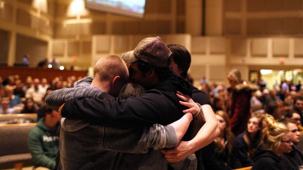 Members of the community pray before the start of the Kalamazoo community prayer service for the shooting victims on Sunday.