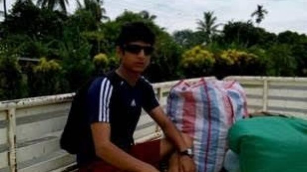 Refugee Loghaman Sawari, 20, pictured in Lae with all his possessions, wants to return to the relative safety of the ...