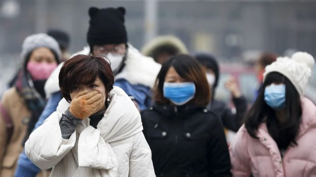 A woman uses her hand to cover her face from pollutants as people walk along a street on a polluted day in Beijing last ...