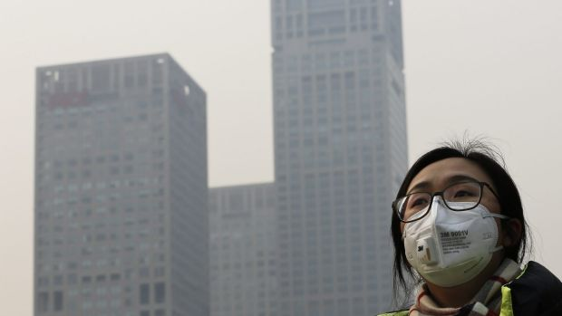 A woman wearing a face mask to protect herself from pollutants walks past office buildings shrouded with pollution haze ...