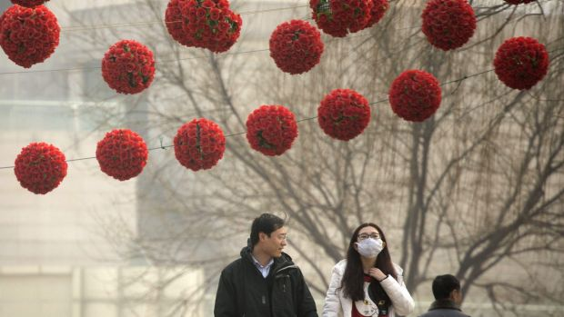A woman wears a mask as she walks through Yuyuantan Park on a heavily polluted day in Beijing in March last year.