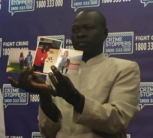 Kuol Atuk's uncle holds photos of the teenager when he was a young boy at Police Headquarters on Tuesday.